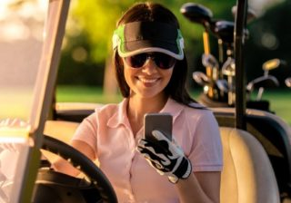 woman using phone app on golf course